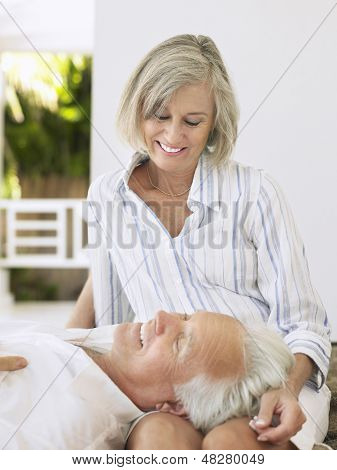 Mature man resting head on woman's lap on verandah