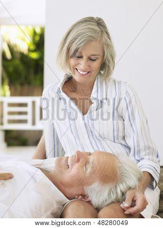Mature man resting head on woman's lap on verandah