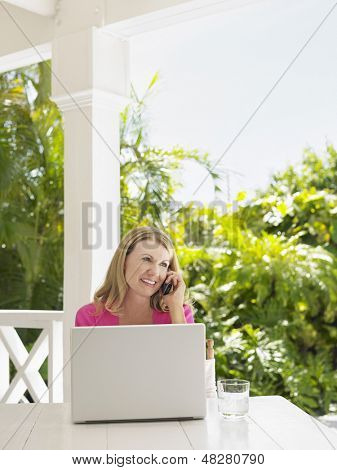 Middle aged woman using mobile phone at verandah table with laptop