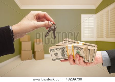Man and Woman Handing Over Cash For House Keys Inside Empty Green Room with Boxes.