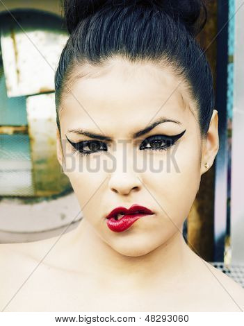 Portrait of young woman punk hipster with red lipstick lip curl and cat style eye liner