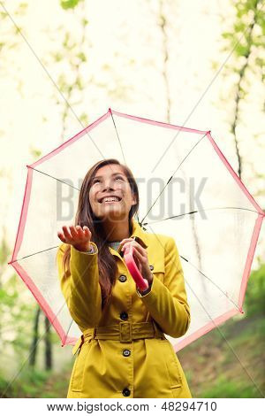 Asian Autumn woman happy after rain walking with umbrella. Female model looking up at clearing sky joyful on rainy fall day wearing yellow raincoat outside in nature forest. Multiracial Asian girl.
