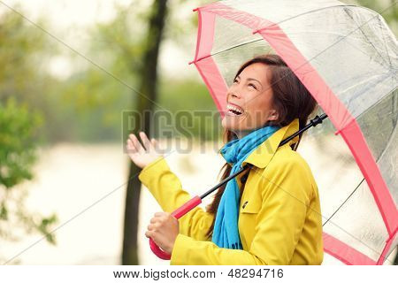 Woman happy with umbrella under the rain during Autumn forest walk. Girl enjoying rainy fall day looking up at sky smiling cheerful. Mixed race Caucasian / Asian chinese girl.