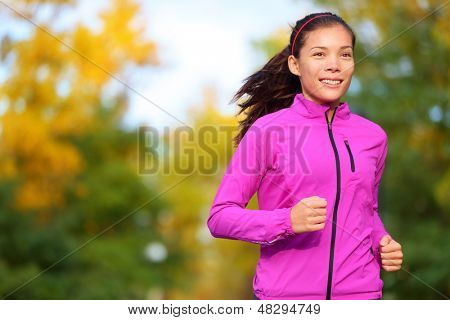Running woman jogging in autumn forest in fall. Beautiful female runner wearing autumn running jacket. Healthy lifestyle photo with beautiful mixed race ethnic Chinese Asian and Caucasian fitness girl