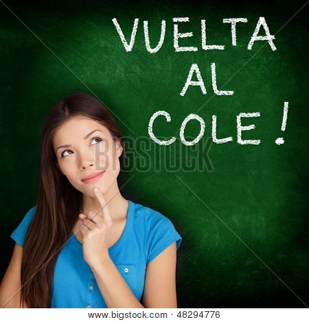 Vuelta al cole - Spanish college university student woman thinking Back to School written in Spanish on blackboard by female on green chalkboard. Spanish language at college or high school.