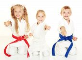 Cheerful young children to sit in a ceremonial kimono karate pose and hit a punch