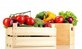 Fresh vegetables in wooden boxes on white background