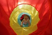 stock photo of long tongue  - Cute little girl entering colourful toy tunnel - JPG