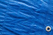 stock photo of eyeleteer  - Blue tarp or waterproof tarpaulin for camping background - JPG