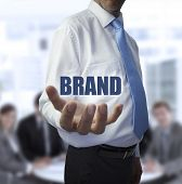 Elegant businessman holding the word brand in front of a business team poster