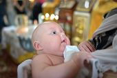 foto of christening  - A portrait of a baby boy during christening ceremony on a golden background of church - JPG