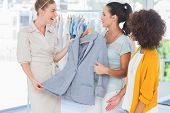 stock photo of blazer  - Smiling women holding a blazer in a creative office - JPG