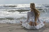 stock photo of rough-water  - Rear view of a young woman meditating on beach facing the ocean - JPG