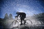 Side view of a mountain bicyclist splashing through water