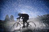 Постер, плакат: Вид сбоку гора велосипедист плескались через воду
