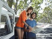 stock photo of campervan  - Full length of happy young couple standing by campervan reading map during road trip - JPG
