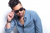 stock photo of tied hair  - closeup of a casual young man holding a hand on his sunglasses while looking away from the camera - JPG