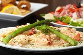 image of antipasto  - A delicious shrimp scampi pasta dish with fried shrimp and antipasto salad in the background.