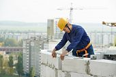 foto of bricklayer  - construction mason worker bricklayer working with limestone brick and measuring tape outdoors - JPG