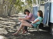 stock photo of campervan  - Happy young couple sitting on deck chairs beside campervan parked at roadside - JPG