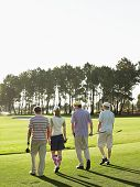 Rear view of young golfers walking on golf course