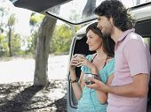 stock photo of campervan  - Happy young woman drinking coffee from thermos cups leaning in open tailgate of campervan - JPG