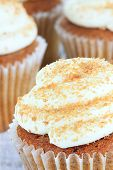 stock photo of sprinkling  - Pumpkin spice cupcakes frosted with cream cheese icing and sprinkled with brown sugar - JPG