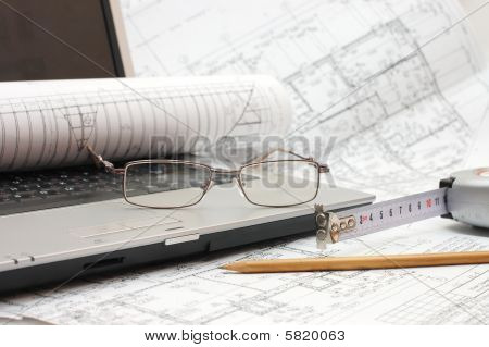 Plans And Laptop with glasses  - construction concept