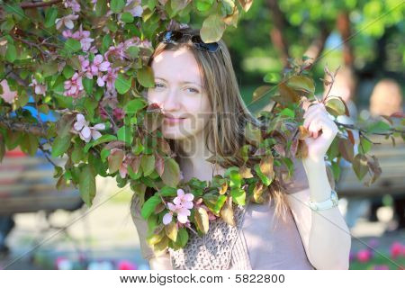 Attractive young woman near flowered tree