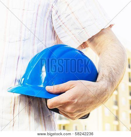 Construction Worker Holding Blue Hard Hat