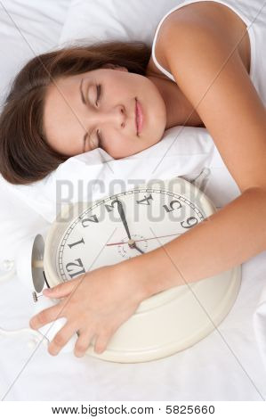 Young Woman Sleeping In White Bed With Alarm Clock