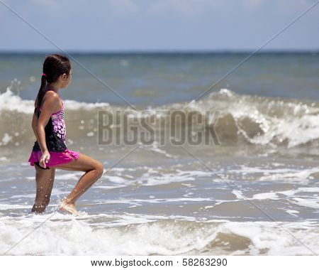 Young Girl Walking Into The Ocean