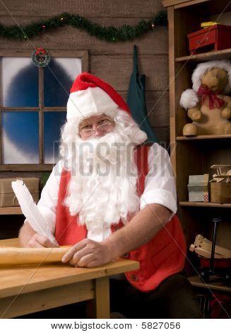 Papai Noel sentado em sua oficina com caneta de pena