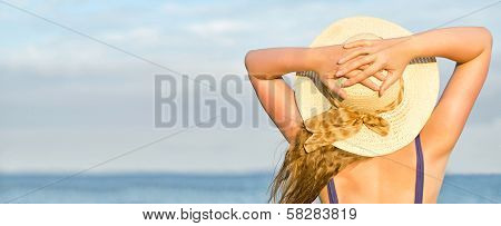 Woman In Straw Hat Sunbathing Near The Sea.