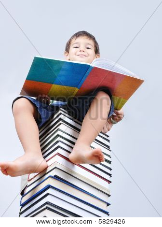 A Little Cute Kid And Large Number Of Books As A Tower
