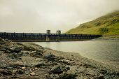 stock photo of hydro  - Gloomy View Of A Hydro Power Station in mountain landscape - JPG