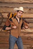 stock photo of western saddle  - a cowboy holding onto his saddle with a serious expression on his face - JPG