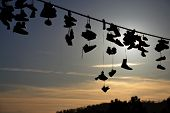 picture of mischief  - Shoes hanging by their shoelaces from a power line.