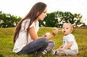 stock photo of feeding  - Young beautiful mother feeding her baby puree outdoors in sunlight - JPG