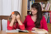 stock photo of homework  - A mother consoles her young daughter when she gets discouraged trying to do her homework - JPG