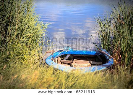 Old Wooden Rowboat On The Shore Of A River