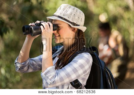 cheerful young woman using binoculars bird watching in forest
