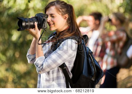 pretty female photographer taking pictures in the nature