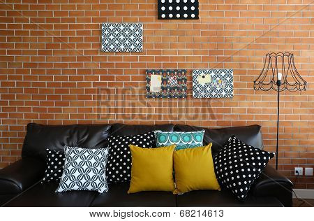 Colorful Pillows On A Sofa With Brick Wall In Background