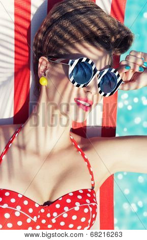 Colorful summer portrait of young attractive woman wearing bikini and sunglasses lying down under a palm tree by the swimming pool
