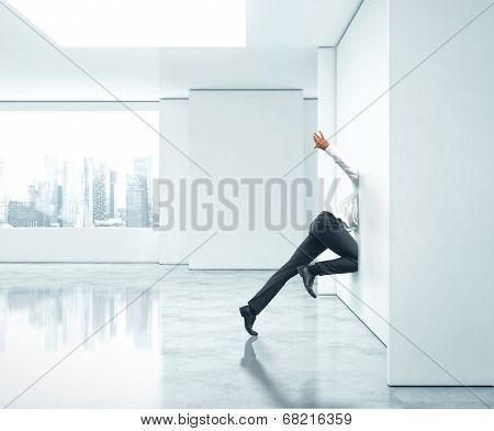 Businessman getting stuck into office wall