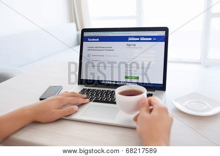 Man Sitting At The Macbook Retina With Site Facebook On The Screen And Drinking Tea