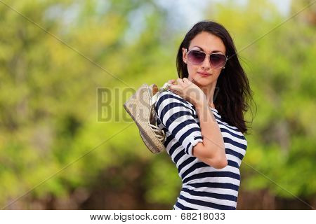 Woman holding her shoes in a nature setting