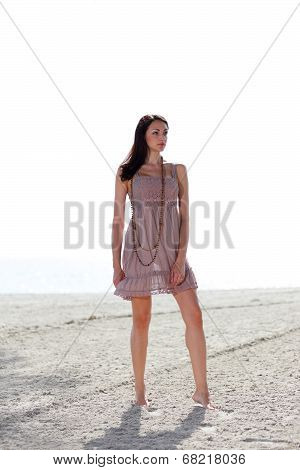Woman posing on the beach in a dress