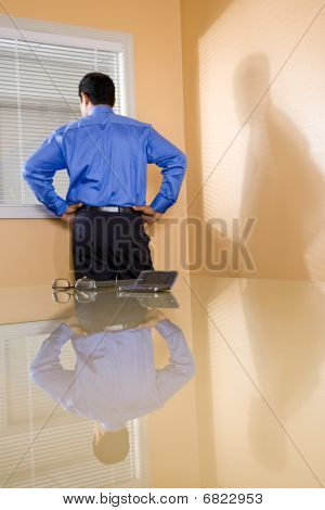 Middle-aged Hispanic businessman looking out office window
